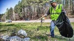 Man picking up roadway litter.
